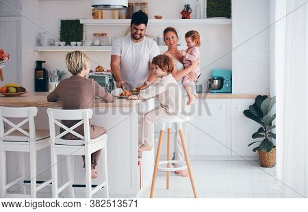 Happy Family With Three Kids Having Breakfast In The Kitchen In The Morning