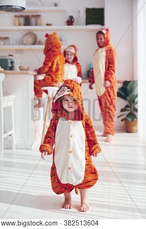 Funny Little Baby Girl Having Fun With Family In Kigurumi Pajamas At Home