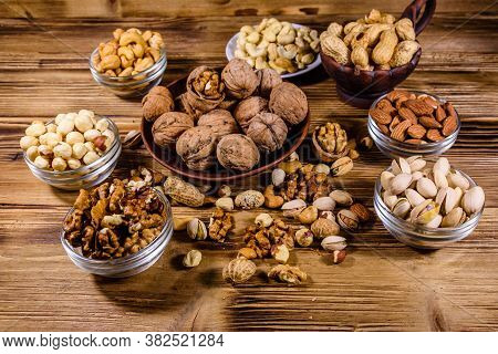 Various Nuts (almond, Cashew, Hazelnut, Pistachio, Walnut) In Bowls On Wooden Table. Vegetarian Meal