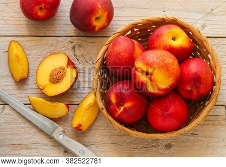 Nectarine. Ripe Juicy Organic Nectarines (peaches) In A Wicker Basket. Whole And Sliced Fruit On A W