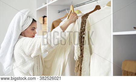 Side View Of Young Adult Woman Standing In Room At White Bathrobe With Towel On Head, Choosing Cloth