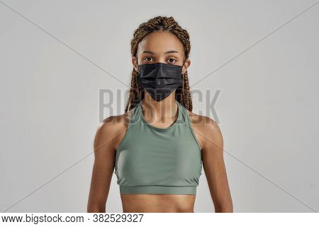 Wear A Mask. Young Sportive Mixed Race Woman Wearing Black Protective Face Mask Looking At Camera Wh