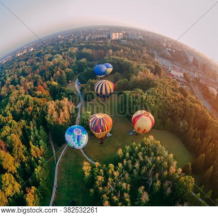 Panoramic Air View Of Hot Air Ballons Prepare For An Early Morning Takeoff From Park In Small Europe