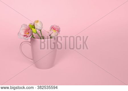 Creative Monochrome Concept Made Of Coffee Or Tea Cup With Tender Pink Eustoma Flowers On Light Pink