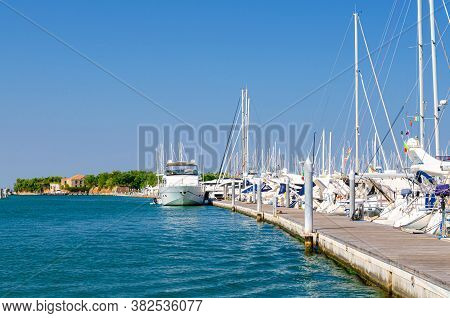 White Yachts Are Moored On Water Of Pier Parking In Marina Port Harbour Of Sottomarina Town And Fort