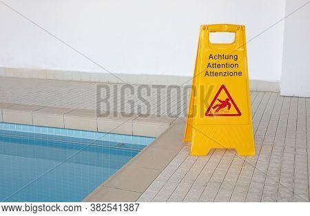 Wet Floor Sign By Indoor Swimming Pool, Selective Focus