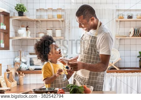 African American Father And Little Son Playing And Laughing During Cooking In Kitchen. Black Family