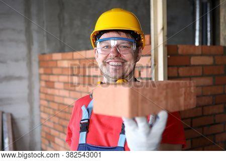 Happy Builder Holds Brick For Masonry And Smiles. Red Brick Masonry. Calculation Amount Necessary Bu