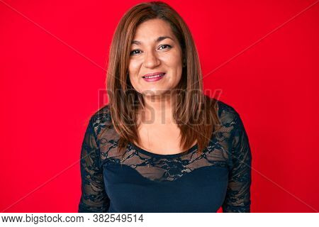 Middle age brunette hispanic woman wearing elegant clothes over red background with a happy and cool smile on face. lucky person.