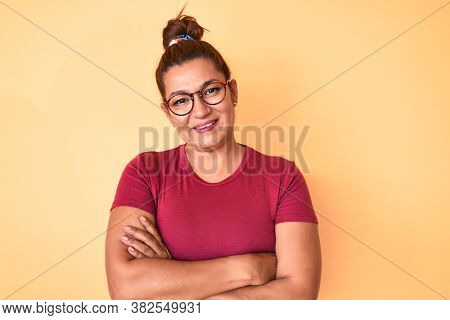 Middle age brunette hispanic woman wearing casual clothes and glasses happy face smiling with crossed arms looking at the camera. positive person.