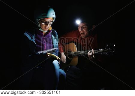 Young Tourists Man And Woman Playing Guitar, Singing And Using Phone App With Chords And Song Lyrics