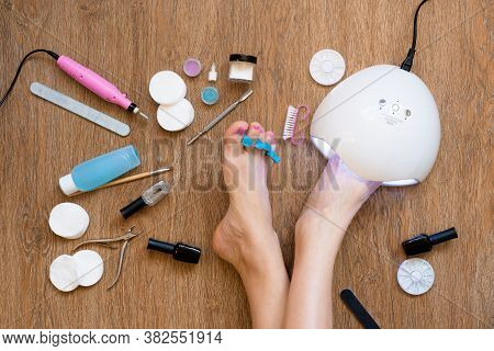 Pedicure At Home Using Nail Polish And Uv Lamps, Nail Files And Scissors. Taking Care Of Yourself An
