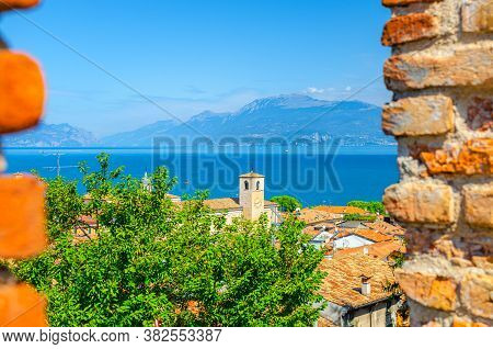 View Of Historical Centre Desenzano Del Garda Old Town With Bell Clock Tower, Lake And Mountain Rang