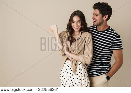 Image of cheerful beautiful couple pointing finger aside and smiling isolated over beige background
