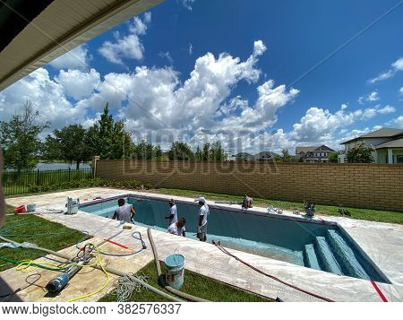 Orlando, Fl/usa-7/7/20: Workers From A Pool Finishing Company Spraying Plaster Finish On The Interio
