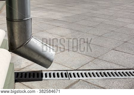 Street Engineering Structure A Downspout Pipe With Drainage Gutter On A Background Of A Gray Stone G
