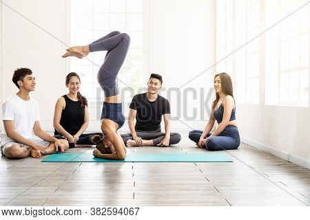 Asian yoga female coach or instructor wear sportswear bra pants show student in fitness studio class  poseture of headstand pose. Yoga Practice Work out exercise and healthy lifestyle concept.