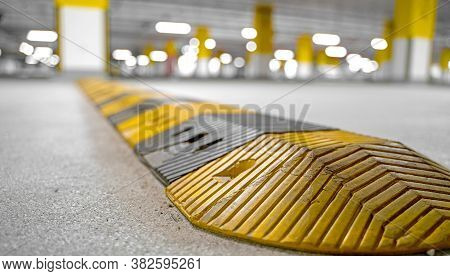 Traffic Safety Speed Bump On An Asphalt Road In A Parking Area. Speed Bumps (or Speed Breakers) Are