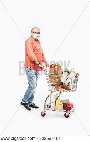 Indian Asian Senior Man Wears Face Mask While Pushing Shopping Trolly Or Cart