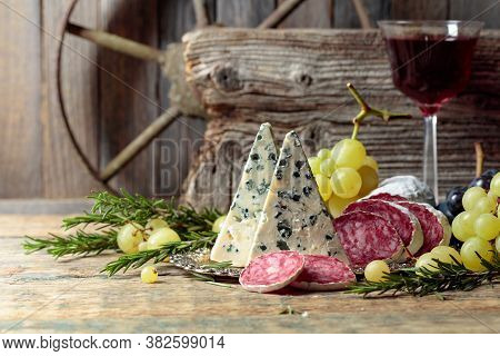 Rustic Still Life With Red Wine And Snacks. On An Old Wooden Table Wine, Blue Cheese, Dry-cured Saus