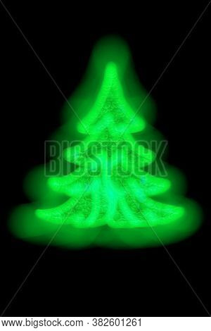 New Year Tree On A Black Background Made Of Blurred Garland Ligths Of Green Color Outdoor At Night.