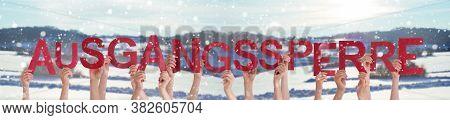 People Hands Holding Word Ausgangssperre Means Curfew, Snowy Winter Background