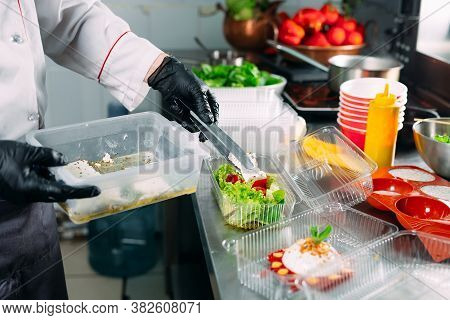 Food Delivery In The Restaurant. The Chef Prepares Food In The Restaurant And Packs It In Disposable