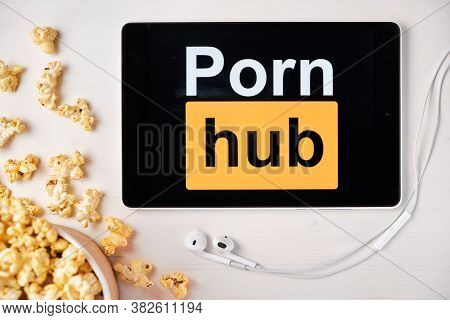 Porn Hub Logo On The Screen Of The Tablet Laying On The White Table And Sprinkled Popcorn On It. App