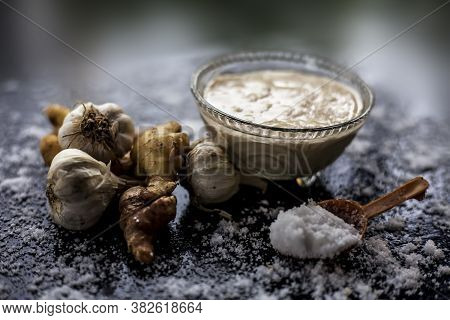 Shot Of Freshly Ground Garlic And Ginger Paste In A Glass Bowl On A Black Surface Along With Raw Gin