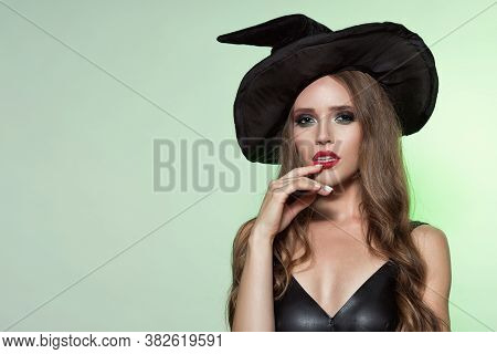 Witch Woman With Long Curly Hair And Perfect Makeup And Red Lips In Witches Black Hat. Green Backgro