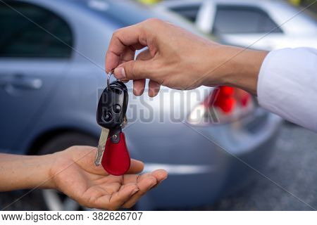 Businessman Handing Over Gives The Car Key For Rental Or Sell To The Customer On Car Background. Sal