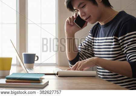 Happy Young Man Learn Language Listen Lecture Watch Webinar Write Notes Look At Laptop Sit In Home,