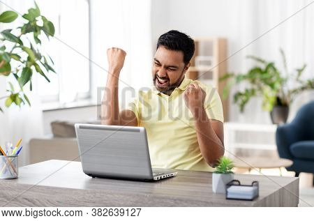 technology, remote job and lifestyle concept - happy smiling indian man with laptop computer working and celebrating success at home office