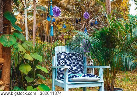 Chair With Designer Cushions In A Garden Decorated For A Party