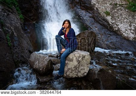 Beautiful Young Woman Hiker Sitting Near Waterfall