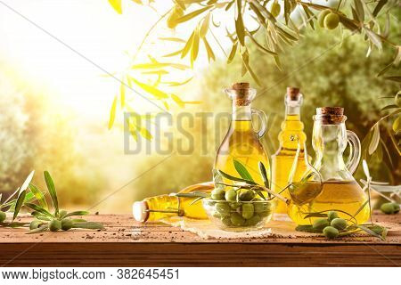 Glass Containers With Olive Oil On Wooden Table With Branches And Olives In Crop Field Full Of Olive