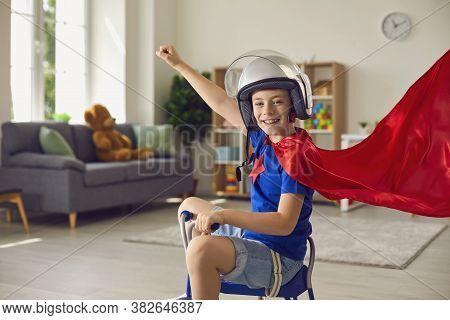Superhero Child. Kids Costume. Childrens Room. Child Boy In Red Cape And Superhero Helmet Plays In N