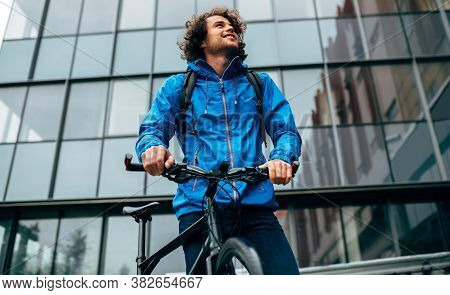 Bottom View Of Man In Blue Raincoat Posing With His Bike After Cycling In The Street On A Rainy Day.