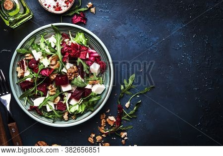 Arugula, Beet And Cheese Salad With Fresh Radicchio And Walnuts On Plate With Fork, Dressing And Spi