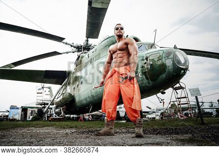 Muscular Man With Sunglasses And Naked Torse Holding Wrenches Near Stationary Soviet Helicopter. Tec