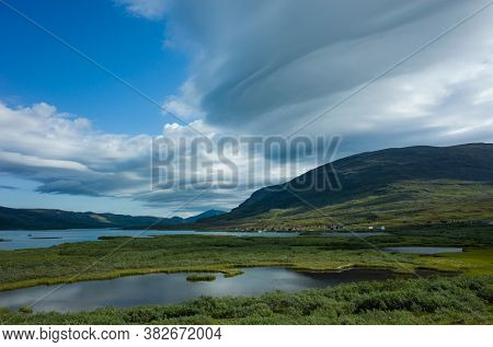 Swedish Lapland landscape. Lake Alisjavri on Kungsleden and Nordkalottruta Arctic hiking Trail in northern Sweden. Arctic environment of Scandinavia in summer day with unusual cloud formation