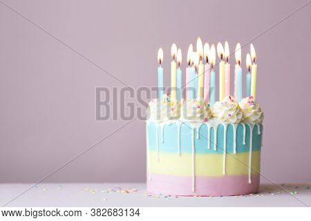 Birthday cake with drip icing and pastel birthday candles