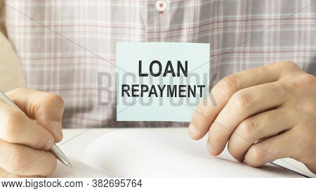 Closeup On Businessman Holding A Card With Loan Repayment Message, Business Concept Image With Soft