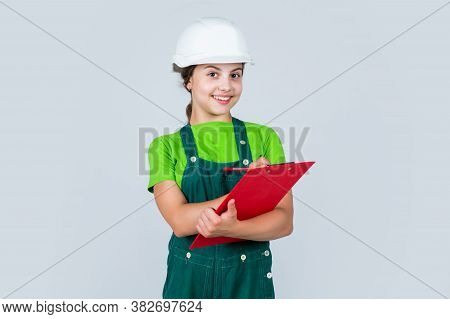 Little Kid In Helmet With Tablet. Repair Planning. Kid In Hard Hat Making Notes. Child Hold Document