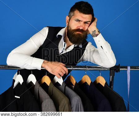 Shop Assistant Or Seller Leans On Clothes Hangers With Suits.