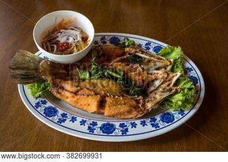 Fried Sea Bass Fish In White Plate With Spicy And Sweet Sauce In Thai Style .  Crispy Thai Style Dee
