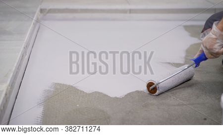Floor Painting. Dirty Repairs And Alterations. A Worker Paints The Floor White With A Roller. The Co