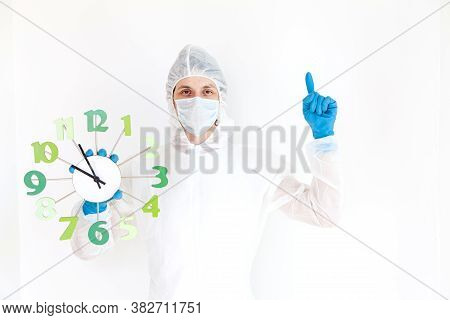 A Man In A Protective Suit, Gloves And Face Mask Is Holding A Watch And Making A Gesture Of Attentio