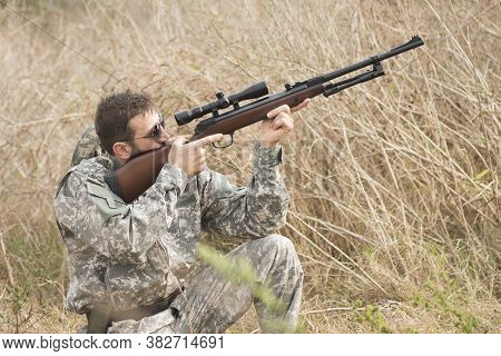 The Hunter In Military Uniform Is Aiming And Shooting A Weapon With Sniper In Dry Bush.