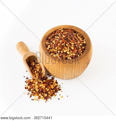 Wooden Bowl And Scoop Full Of Crushed Red Cayenne Pepper, Dried Chili Flakes And Seeds Isolated On W